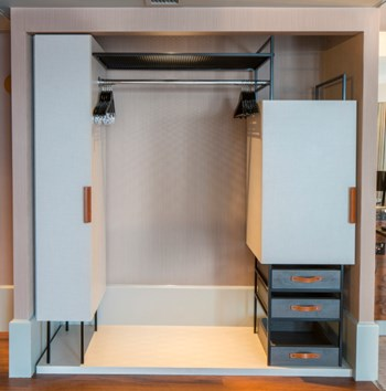 Hotel bedroom open wardrobe with hanging rail, drawers and minibar