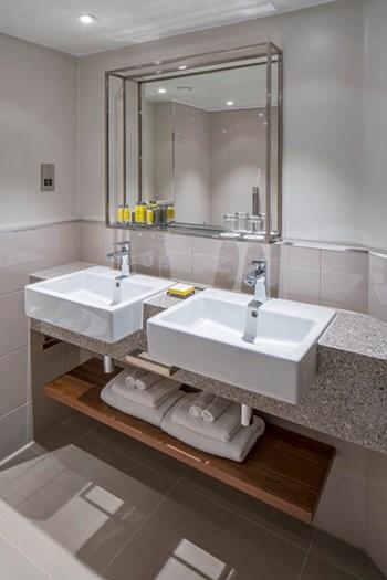 Bathroom vanity unit double sink and wooden towel shelf