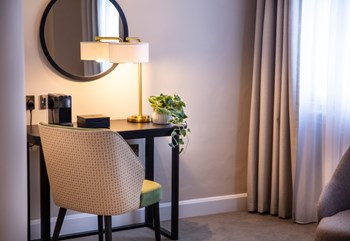 Hotel bedroom desk with circular mirror above