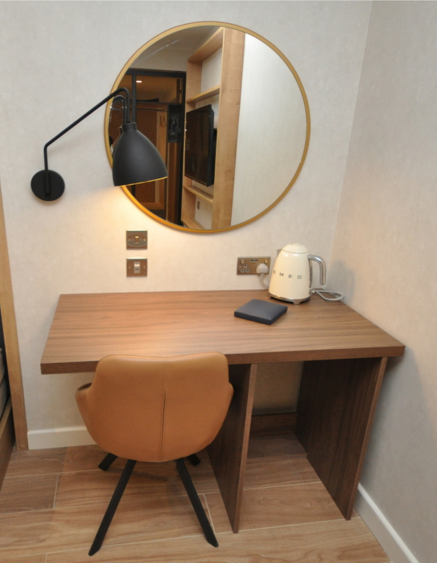 Hotel bedroom desk, chair and circular mirror