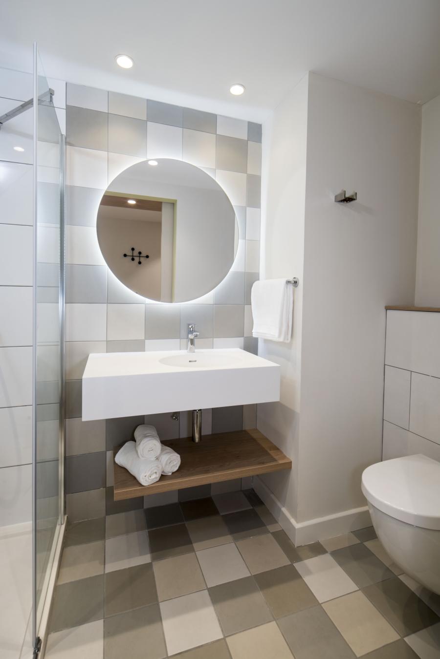 Hotel bathroom vanity unit and circular mirror
