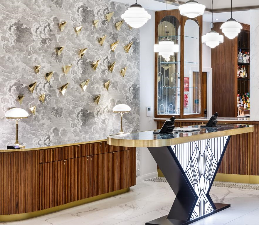 Metal fretwork on backlit perspex for the oval hotel reception desk. Walnut curved credenza with matching brass edging.